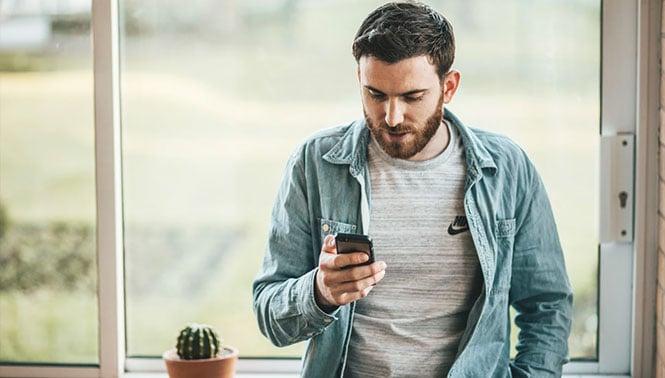 Ein junger Mann mit blauem Jeanshemd und Smartphone in der Hand